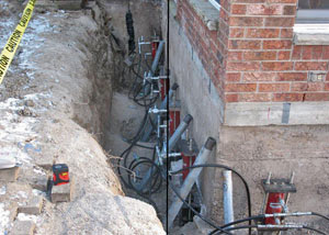 Foundation push piers installed around a house with a foundation settlement issues in Stratford