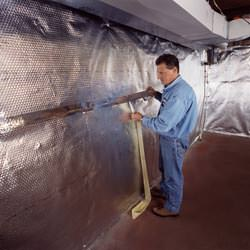 Installation of a radiant heat and vapor barrier on a basement wall in Candian